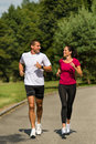Caucasian couple running in park sporty Stock Photography