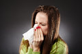 Caucasian female with flu blowing her nose young woman bad cold in a white tissue Stock Photos