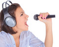 Caucasian female singing in to microphone beauty Royalty Free Stock Image