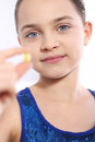 Caucasian girl holding a yellow pill Royalty Free Stock Photo
