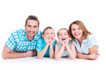 Caucasian happy smiling young family with two children lying down on the floor Royalty Free Stock Photos