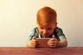 Caucasian kid looking at the smartphone screen