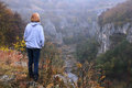 Caucasian lady on the edge of the canyon a woman stands emen in bulgaria a raw foggy morning in fall Stock Images