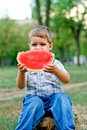 image photo : Caucasian little boy eats a slice of watermelon