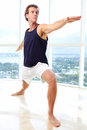 Caucasian male doing yoga warrior pose indoors in high rise apartment Royalty Free Stock Photos