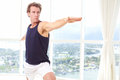 Caucasian male doing yoga warrior pose indoors in high rise apartment Stock Photos