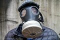 Caucasian male flat cap puffy black coat wearing israeli gas mask against concrete wall Royalty Free Stock Image