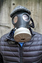 Caucasian male flat cap puffy black coat wearing israeli gas mask against concrete wall Royalty Free Stock Photography