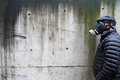 Caucasian male flat cap puffy black coat wearing israeli gas mask against concrete wall Royalty Free Stock Photos