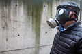 Caucasian male flat cap puffy black coat wearing israeli gas mask against concrete wall Stock Photos