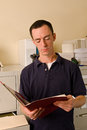 Caucasian male office worker file room reading papers inside folder Stock Photography