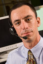 Caucasian male receptionist wearing headset looking toward camera Stock Photo