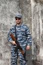 Caucasian man with black sunglasses in urban warfare holding gri grifle near wall Stock Photography