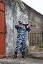 Caucasian man with black sunglasses in urban warfare holding rif rifle near gate Stock Photo