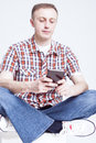 Caucasian Man in Checkered Shirt and Jeans Chatting on Cellphone Against White Background. Royalty Free Stock Photo