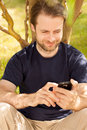 Caucasian man looking on a mobile phone outdoor happy smiling forty years old in park while sitting by tree Royalty Free Stock Photography