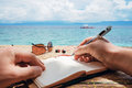 Caucasian man is writing sime idea, message or letter in his notepad by pen while he sitting on the beach of tropical Royalty Free Stock Photo