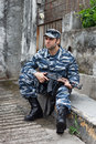 Caucasian military man in urban warfare sitting and holding auto automatic weapon selective focus Stock Images