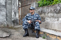 Caucasian military man win urban warfare si with black sunglasses in sitting and holding rifle Royalty Free Stock Image