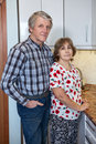 Caucasian positive retirement mature couple standing beside kitchen countertop and looking at camera Royalty Free Stock Photo