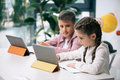 Caucasian schoolkids using digital tablets while studying together in class Royalty Free Stock Photo