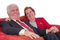 Caucasian senior couple smiling and holding hands wearing elegant clothes while sitting on a comfortable red couch Royalty Free Stock Images