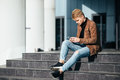 Caucasian student sitting on steps and using smartphone Royalty Free Stock Photo