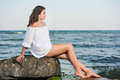 Caucasian teen girl in bikini and white shirt lounging on lava rocks by the ocean teenage sitting a rock Stock Photo