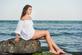 Caucasian teen girl in bikini and white shirt lounging on lava rocks by the ocean teenage sitting a rock Royalty Free Stock Photo