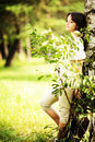 Caucasian teen girl with dark hair is standing near a tree with sad or dreamy face. Looking away. Royalty Free Stock Photo