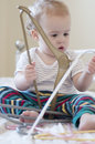 Caucasian toddler sat on bed playing with coat han cute wearing stripes hangers Royalty Free Stock Image