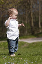 Caucasian toddler stood on grass cute wearing white shirt and jeans sunny day Stock Photo