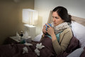 Caucasian woman having bad cold sitting in bed Stock Photo