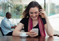 Caucasian woman surfing the internet and drinking coffee in a cafeteria Royalty Free Stock Photo