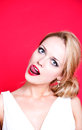 Caucasian woman wearing white dress on red background licking her lips Royalty Free Stock Photo