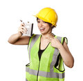 Caucasian young adult woman in her mid s wearing reflective yellow safety helmet and safety vest holding a hip flask while Royalty Free Stock Photos