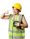 Caucasian young adult woman in her mid s wearing reflective yellow safety helmet and safety vest holding a hip flask and looking Stock Images