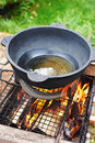Cauldron of oil for pilaf on lattice of barbecue. Royalty Free Stock Photos