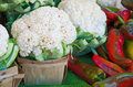 Cauliflower and red peppers cauliflowers heads in produce boxes with at the farmer s market Stock Images