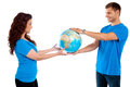 Causal young couple holding globe together Stock Photos
