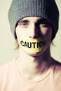 Caution boy young man with mouth sealed Royalty Free Stock Photos