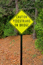 Caution pedestrians on bridge sign a bright yellow with a dense forest in the background Stock Image