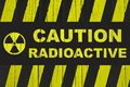 `Caution, radioactive` warning sign written in bold letters with radiation symbol and yellow and black stripes Royalty Free Stock Photo