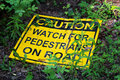 A caution watch for pedestrians on the road sign laying on the ground Royalty Free Stock Photo