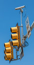 Cctv surveillance security camera with the traffic light and si sign against a blue sky Royalty Free Stock Photography