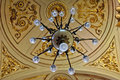 Ceiling mounted chandelier hanging from a decorative Stock Images