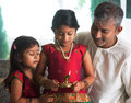 Celebrate diwali or deepavali at home indian family in traditional sari little girl hands holding oil lamp during festival of Stock Photography