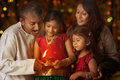 Celebrating diwali indian family in traditional sari lighting oil lamp and fesitval of lights inside a temple little girl hands Stock Images