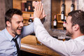 Celebrating success together two cheerful young men in shirt and tie talking to each other and gesturing while drinking beer at Stock Photos