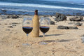 Celebration with two glasses of red wine on the ni and a bottle beach in canary islands spain Royalty Free Stock Images